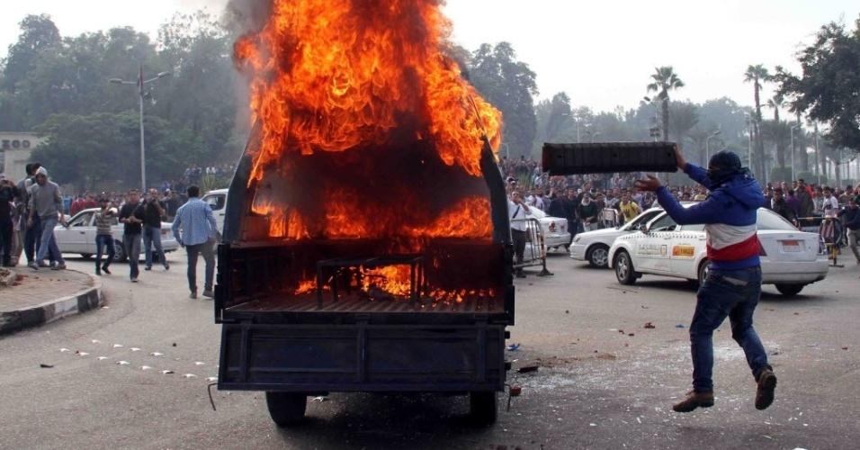 01.dez.2013 - Um estudante egípcio da Universidade do Cairo depreda um carro da polícia durante manifestação em apoio a um estudante de engenharia morto na última semana em confrontos com as forças de segurança egípcias