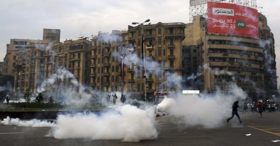 1.dez.2013 - Partidários da Irmandade Muçulmana e do presidente egípcio deposto Mohamed Mursi fogem de gás lacrimogêneo disparados pela polícia na praça Tahrir, no Cairo, Egito. Forças de segurança egípcias usaram gás para dispersar manifestantes que protestavam contra o governo apoiado pelo Exército