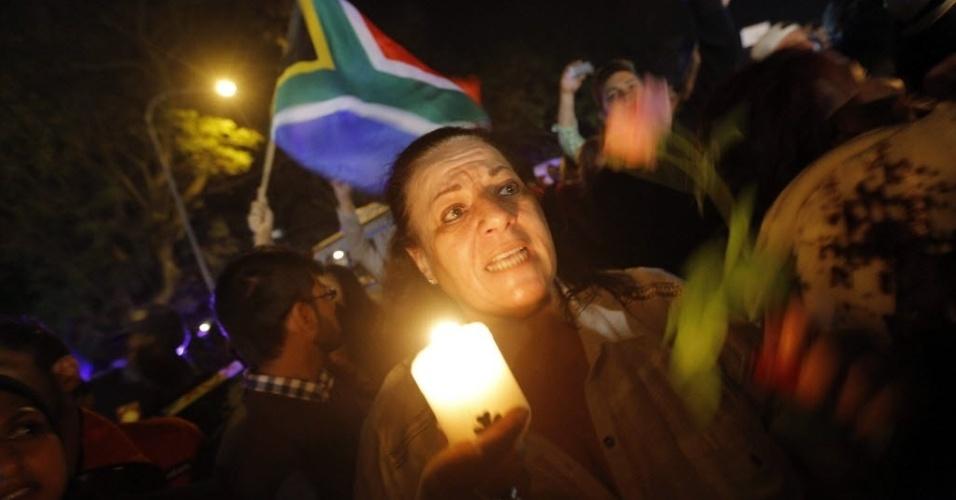 05.dez.2013 - Pessoas cantam em homenagem a Nelson Mandela em frente à casa do ex-presidente sul-africano, em Johannesburgo, na noite desta quinta-feira (5), após sua morte, aos 95 anos