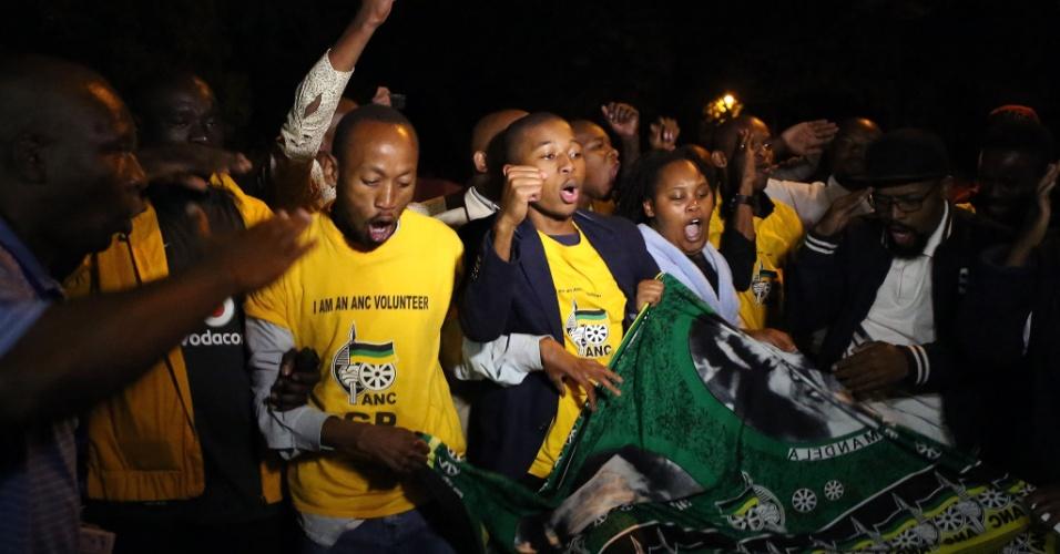 05.dez.2013 - Pessoas cantam em homenagem a Nelson Mandela em Johannesburgo, após a notícia da morte do presidente sul-africano
