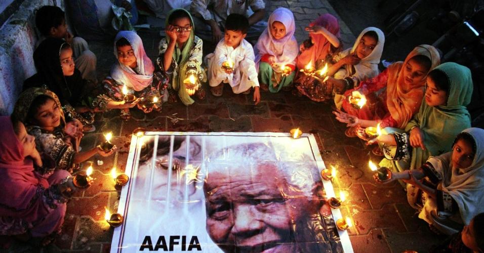 6.dez.2013 - Crianças seguram velas durante homenagens ao ex-presidente da África do Sul, Nelson Mandela, na região portuária de Karachi, no sul do Paquistão, nesta sexta-feira (6). Mandela morreu nessa quinta (5) em sua casa, em Johannesburgo, aos 95 anos