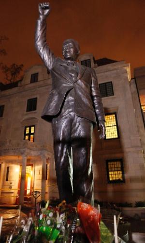 6.dez.2013 - Flores são depositadas em frente à estátua do ex-presidente africano Nelson Mandela na embaixada sul-africana em Washington (EUA)