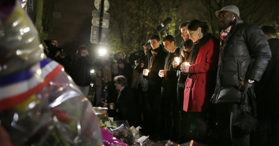 6.dez.2013 - Líder da organização não governamental francesa SOS Racismo, Cindy Leoni (de vermelho), segura vela e reza em respeito ao ex-presidente sul-africano Nelson Mandela, nesta sexta-feira (6), em frente à embaixada da África do Sul em Paris, um dia após a morte do mandatário
