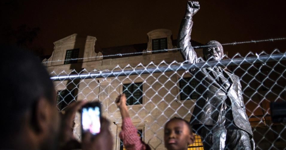 6.dez.2013 - Pai fotografa filho de 10 anos em frente à estátua de Nelson Mandela na embaixada sul-africana em Washington (EUA)