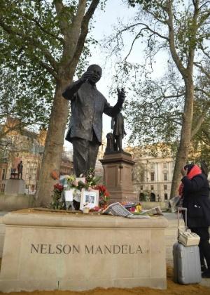 6.dez.2013 - Pessoas deixam homenagem em estátua do ex-presidente Sul-Africano Nelson Mandela na praça do Parlamento em Londres, Inglaterra