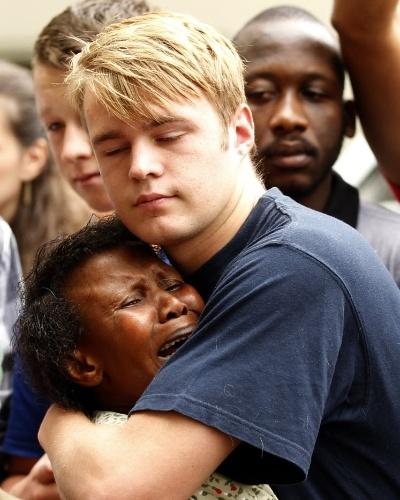 6.dez.2013 - Pessoas se abraçam em frente à casa de Nelson Mandela, em Johannesburgo, na África do Sul, nesta sexta-feira (6)
