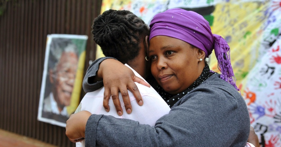 6.dez.2013 - Sul-africanas se consolam pela morte de Nelson Mandela, em frente à casa onde o ex-presidente sul-africano morou em Soweto, Johannesburgo