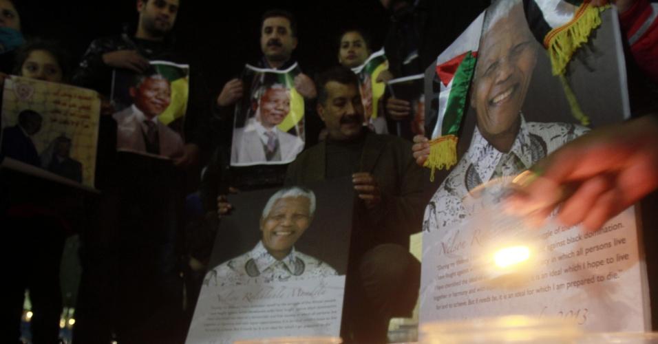 7.dez.2013 - Palestinos carregam fotografias do falecido líder da África do Sul, Nelson Mandela, durante vigília em praça, neste sábado (7), na Palestina. A população presta homenagens ao líder, morto na quinta-feira (5). O cortejo fúnebre a Mandela durará três dias em Pretória, na África do Sul