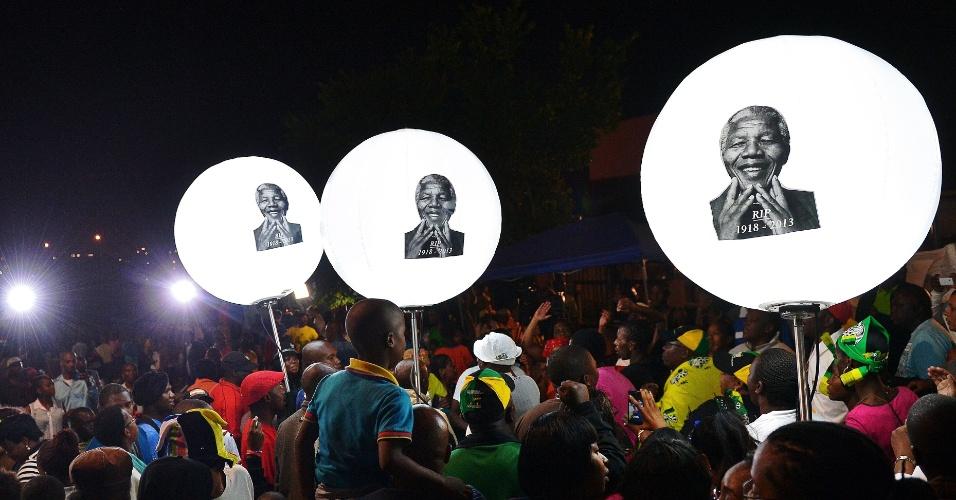 7.dez.2013 - Pessoas seguram balões iluminados com a imagem do ex-presidente da África do Sul, Nelson Mandela, neste sábado (7), em frente a casa do líder em Johanesburgo. A população presta homenagens ao líder, morto na quinta-feira (5). O cortejo fúnebre a Mandela durará três dias em Pretória