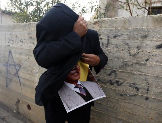 7.dez.2013 - Um manifestante palestino segura um pôster do líder sul-africano Nelson Mandela durante uma manifestação contra assentamentos judeus na vila de Nabi Saleh, na Cisjordânia. Mandela morreu na quinta-feira (5) e terá um cortejo fúnebre de três dias em Pretória, na África do Sul