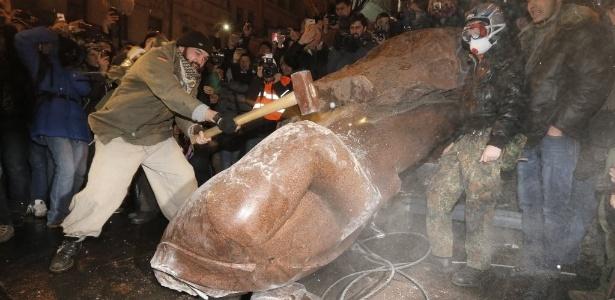 Manifestante usa marreta contra estátua de Vladimir Lênin, símbolo da Revolução Russa, derrubada na praça da Independência de Kiev, após nova manifestação