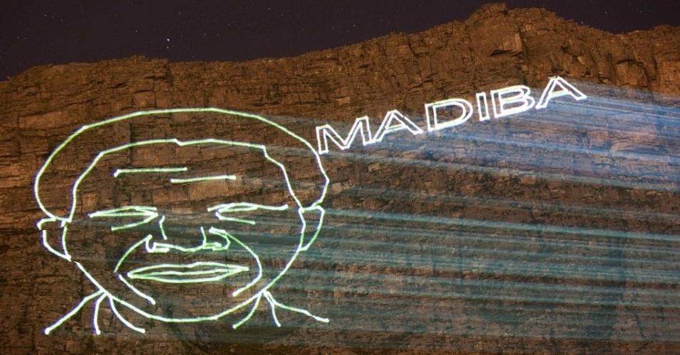 09.dez.2013 - Imagem do ex-presidente da África do Sul, Nelson Mandela, e do nome de seu clã é projetada na Table Mountain, montanha da Cidade do Cabo, neste domingo (8), três dias após a morte do líder sul-africano