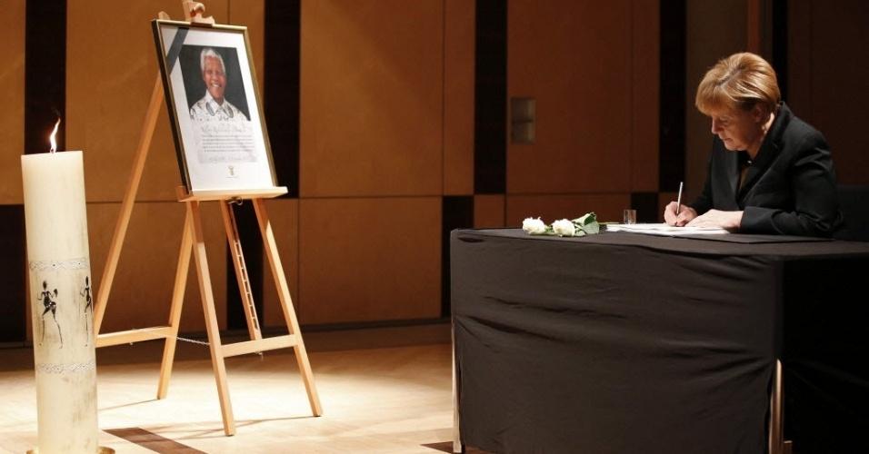 9.dez.2013 - A chanceler alemã, Angela Merkel, assina livro de condolências do ex-presidente sul-africano Nelson Mandela, na embaixada do país em Berlim, na Alemanha