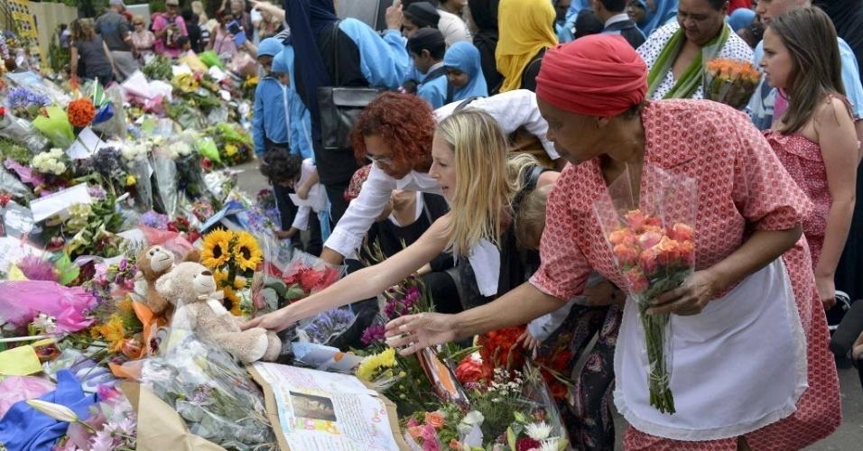 9.dez.2013 - Pessoas homenageiam Nelson Mandela próximo sua casa em Johannesburgo, nesta segunda-feira (9). Centenas de sul-africanos continuam peregrinando ao local, onde deixam suas mensagens de reconhecimento a Mandela e cantam e dançam lembrando seu legado