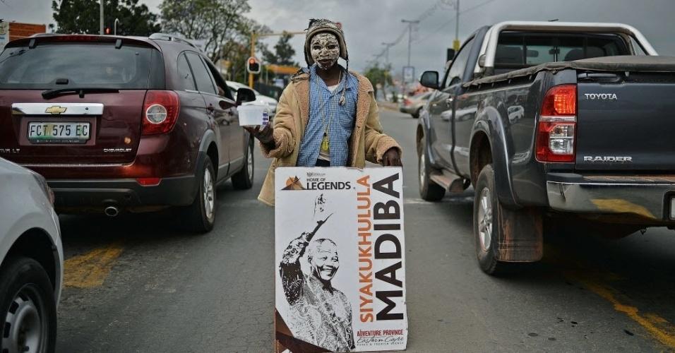 9.dez.2013 - Uma criança de rua segura um cartaz com a imagem do ex-presidente sul-africano Nelson Mandela, enquanto pede esmolas durante horário de pico em Mthata, perto da casa de Mandela, em Qunu, nesta segunda-feira (9). Qunu é o vilarejo onde o líder nasceu e onde será enterrado, em 15 de dezembro