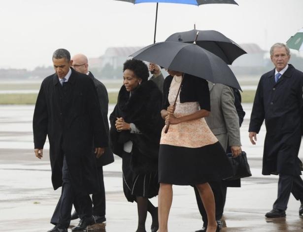 10.dez.2013 - O presidente dos EUA, Barack Obama, e o e ex-presidente George W. Bush são recebidos por funcionários em sua chegada à Base Aérea de Waterkloof, Pretória, África do Sul. Autoridades prestam homenagens ao ex-presidente Nelson Mandela durante funeral nesta terça-feira