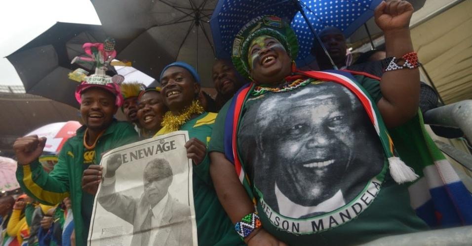 10.dez.2013 - Pessoas seguram cartazes com fotos de Nelson Mandela durante cerimônia em homenagem ao líder sul-africano no estádio Soccer City, em Johannesburgo