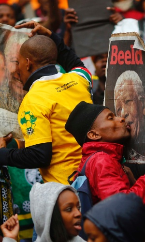 10.dez.2013 - Sul-africanos beijam fotografias do ex-presidente Nelson Mandela, nesta terça-feira (10), enquanto aguardam o início da cerimônia fúnebre pública no estádio FBC --mais conhecido como Soccer City--, em Soweto, Johannesburgo (África do Sul). Nelson Mandela morreu no último dia 5, aos 95 anos