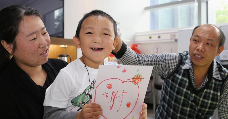 """11.dez.2013 - Guo Bin, 6, exibe um papel com o texto """"Obrigado"""" ao lado dos pais nesta quarta-feira (11) no hospital C-Mer Dennis Lam Eye, em Shenzhen (China). Guo teve os olhos arrancados em 24 de agosto por uma mulher, que seria sua tia e que o atraiu para uma área isolada em Shanxi. Ele recebeu alta nesta quinta-feira (12) após receber olhos de prótese, que têm aparência normal, mas que não recuperam sua visão"""
