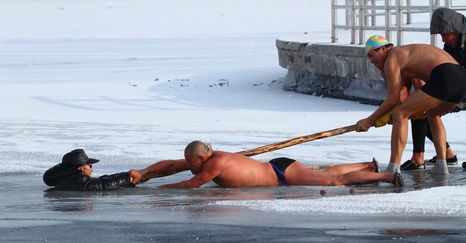 12.dez.2013 - Banhistas ajudam a resgatar homem que caiu em um lago parcialmente congelado, em Changchun, na China. A foto foi tirada no dia 10