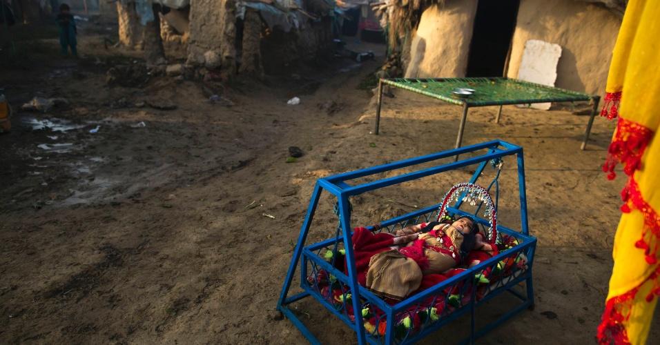 12.dez.2013 - Bebê descansa em berço, nesta quinta-feira (12), em uma favela nos arredores de Islamabad, no Paquistão