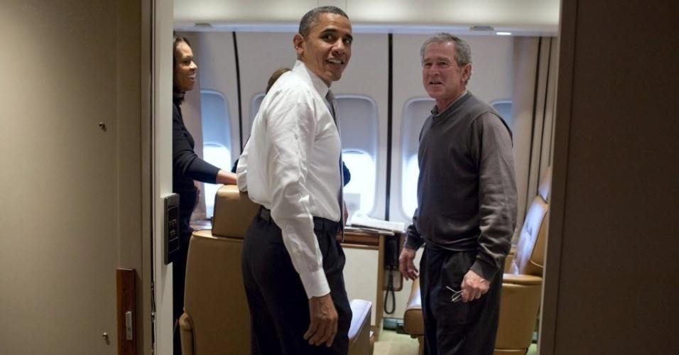 12.dez.2013 - Em foto divulgada pela Casa Branca nesta quinta-feira (12), o presidente dos Estados Unidos, Barack Obama, é acompanhado pelo seu antecessor, George W. Bush, no avião presidencial Air Force One a caminho de Johannesburgo, na África do Sul, onde participaram do funeral de Nelson Mandela na última terça (10)