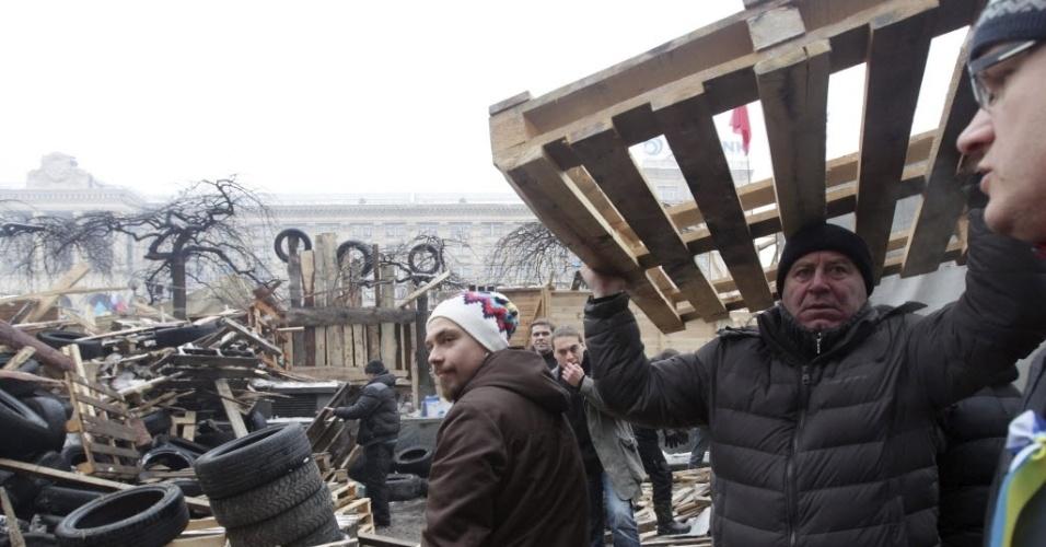 12.dez.2013 - Manifestantes montam barricadas nesta quinta-feira (12) na Praça da Independência, em Kiev, capital da Ucrânia, onde estão acampados. Erguidas para repelir possíveis ataques da polícia, as barreiras chegam a ter mais de três metros de altura. Os ativistas protestam contra a decisão do governo de suspender a assinatura do Acordo de Associação da Ucrânia com a União Europeia