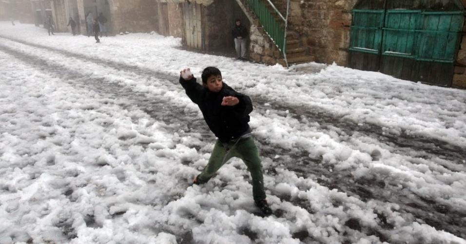 12.dez.2013 - Menino palestino lança uma bola de neve perto da mesquita Ibrahimi, também conhecida como túmulo do patriarca Abraão, um local sagrado para muçulmanos e judeus, na cidade de Hebron, nesta quinta-feira (12). A tempestade de neve fechou estradas e escolas no Oriente Médio