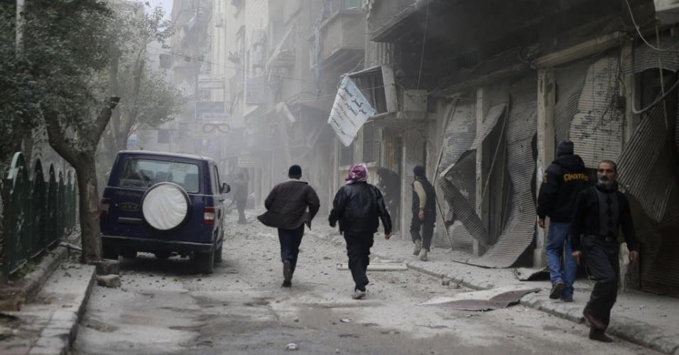 12.dez.2013 - Moradores do bairro de Duma, em Damasco, caminham em local atingido nesta quinta-feira (12) por um ataque aéreo que teria sido feito por forças leais ao presidente sírio, Bashar al-Assad. A Síria vive uma guerra civil