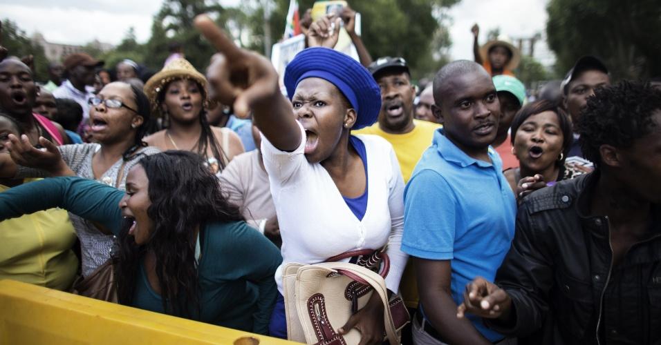 12.dez.2013 - Mulher reage ao saber que o tempo para ver o corpo do ex-presidente sul-africano Nelson Mandela está acabando no Union Buildings, em Pretória, na África do Sul. Longas filas se formaram nesta quinta-feira (12) para ver o corpo do líder sul-africano