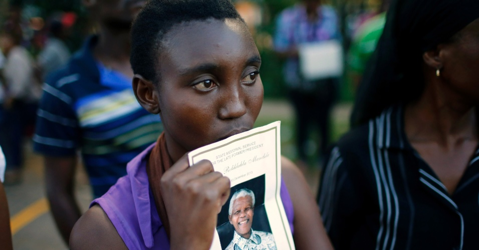 12.dez.2013 - Mulher segura foto do ex-presidente sul-africano Nelson Mandela do lado de fora do Union Buildings. Milhares de pessoas foram ao local, na cidade de Pretória, prestar suas últimas homenagens ao líder sul-africano