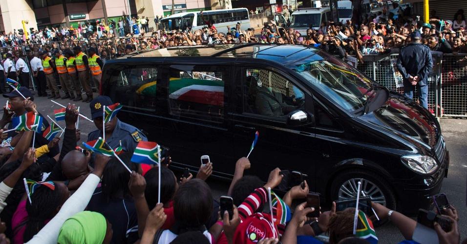 12.dez.2013 - Público observa carro que leva o caixão com o corpo do ex-presidente sul-africano Nelson Mandela nesta quinta-feira (12) em Pretória. Milhares de pessoas fizeram fila nesta quarta (11) para se despedir do ex-líder, e outras milhares são esperadas nesta quinta