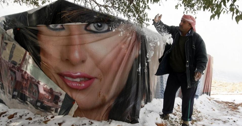 12.dez.2013 - Refugiado sírio remove neve acumulada em sua tenda nesta quinta-feira (12) no Vale do Bekaa, no Líbano. O Acnur (Alto Comissariado das Nações Unidas para Refugiados) promete distribuir tapetes, cobertores e colchões para os refugiados afetados pelo frio na região