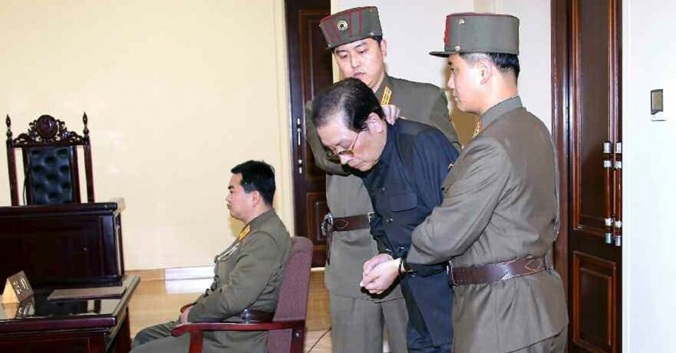 13.dez.2013 - Jang Song Thaek, tio do líder norte-coreano, Kim Jong Un, comparece a tribunal militar em Pyongyang com as mãos amarradas e escoltado