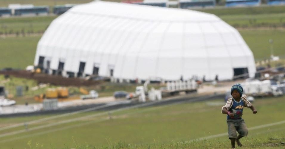 13.dez.2013 - Menino caminha em uma colina do vilarejo de Qunu com a instalação onde será celebrado o enterro do corpo do ex-presidente da África do Sul Nelson Mandela no próximo domingo (15)