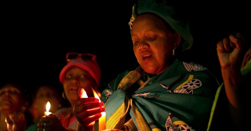 13.dez.2013 - Mulher participa de vigília noturna próxima à penitenciária de segurança máxima da costa da Cidade do Cabo, na África do Sul, aonde Nelson Mandela ficou preso, em homenagem ao presidente sul-africano