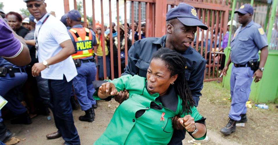 13.dez.2013 - Policial auxilia mulher que ficou ferida durante empurra-empurra na entrada do Union Buildings, onde é velado o corpo do ex-presidente sul-africano Nelson Mandela, em Pretória, África do Sul