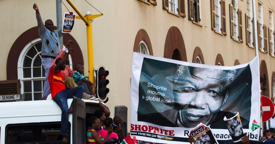 13.dez.2013 - Sul-africanos exibindo imagem de Nelson Mandela dançam e cantam em homenagem ao ex-presidente morto no último dia 5, enquanto caminham até o Union Buildings