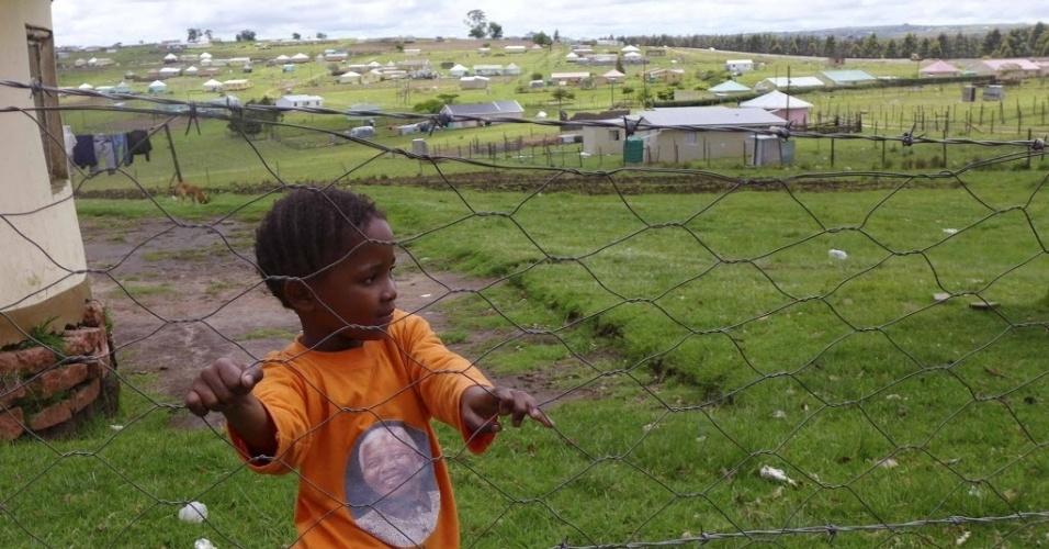 13.dez.2013 - Vestida com uma camisa que homenageia Nelson Mandela, menina observa as equipes da imprensa internacional que chegam  ao vilarejo de Qunu, onde o ex-presidente da África do Sul será enterrado no próximo domingo (15)