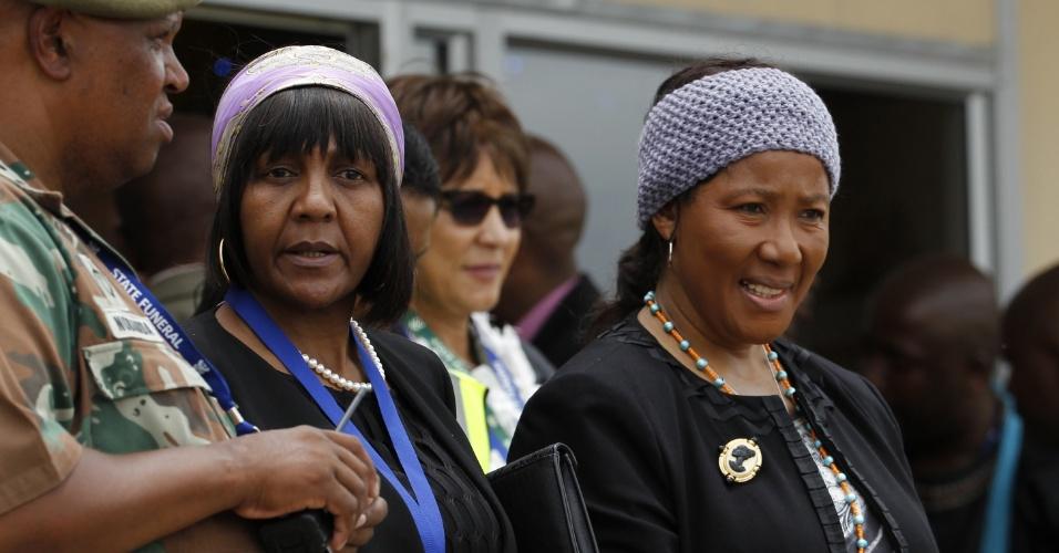 14.dez.2013 - A filha mais velha de Nelson Mandela, Makaziwe (dir.), e a neta dele Ndileka (esq.), acompanham cortejo fúnebre com o corpo do ex-líder sul-africano. O corpo de Mandela será enterrado na vila de Qunu neste domingo (15)
