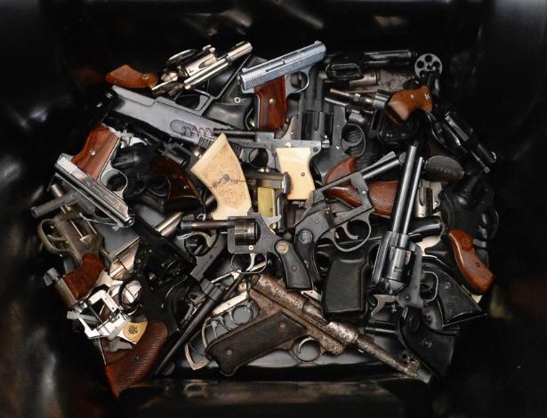 14.dez.2013 - Armas de fogo são colocadas em cesto de lixo durante um programa para devolução de armas em Los Angeles, Califórnia (Estados Unidos). Organizada por Eric Garcetti, prefeito de Los Angeles, a campanha tem como objetivo reduzir a ação de gangues na cidade. O município paga até US$ 200 (cerca de R$ 467), dependendo do calibre da arma