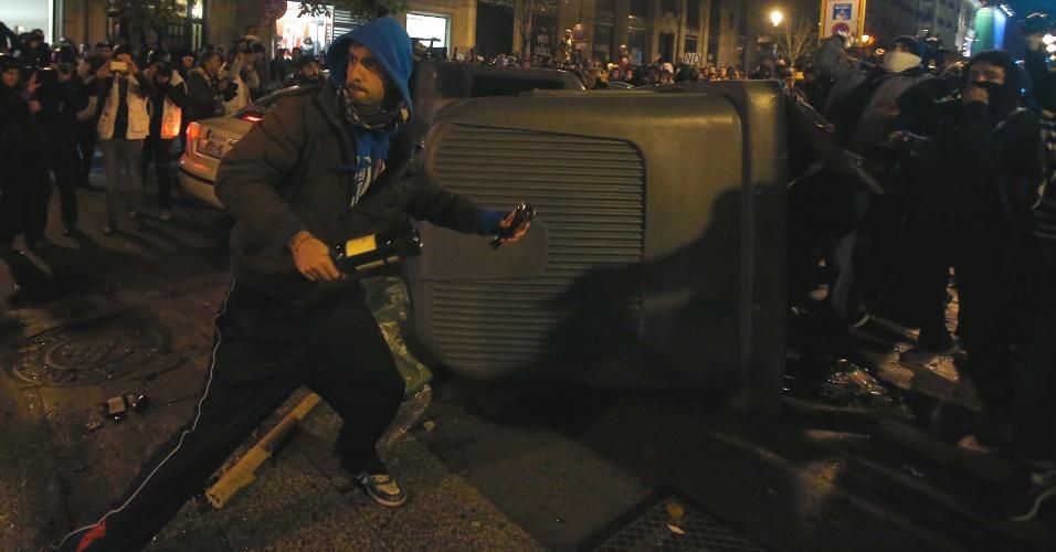 14.dez.2013 - Manifestante em Madrid, na Espanha, se prepara para atirar garrafas enquanto policiais tentam dispersar um protesto contra o governo do país