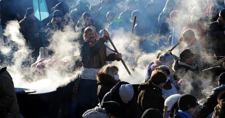 14.dez.2013 - Manifestantes cozinham na praça da Independência em Kiev, Ucrânia. A capital do país vive momentos de tensão, já que apoiadores do presidente Viktor Yanukovych se preparam para protestar nas proximidades do acampamento de manifestantes que pedem a renúncia dele