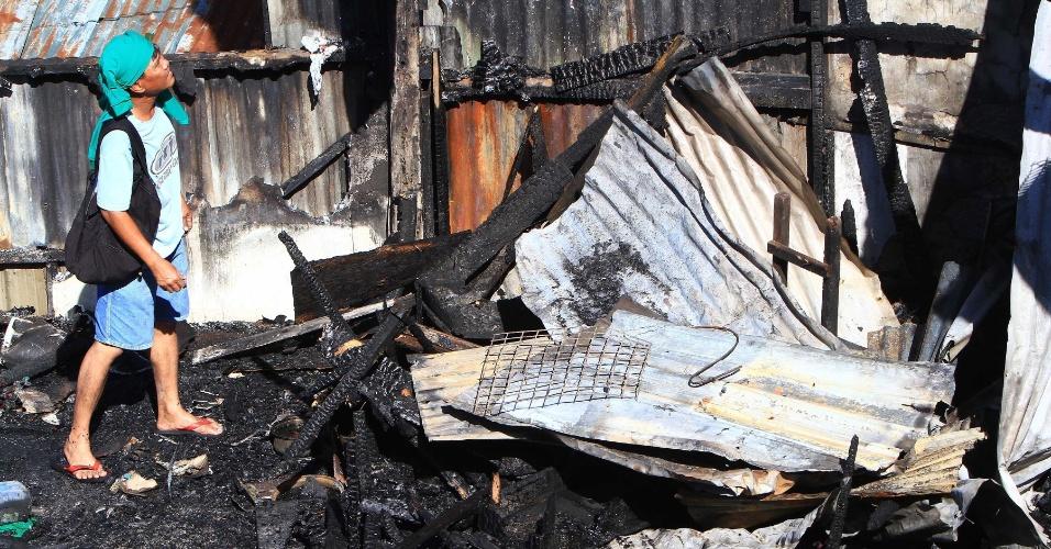 14.dez.2013 - Morador tenta salvar pertences após incêndio em um bairro residencial em Quezon City, nas Filipinas. Cerca de 200 famílias ficaram desabrigadas por causa do incêndio