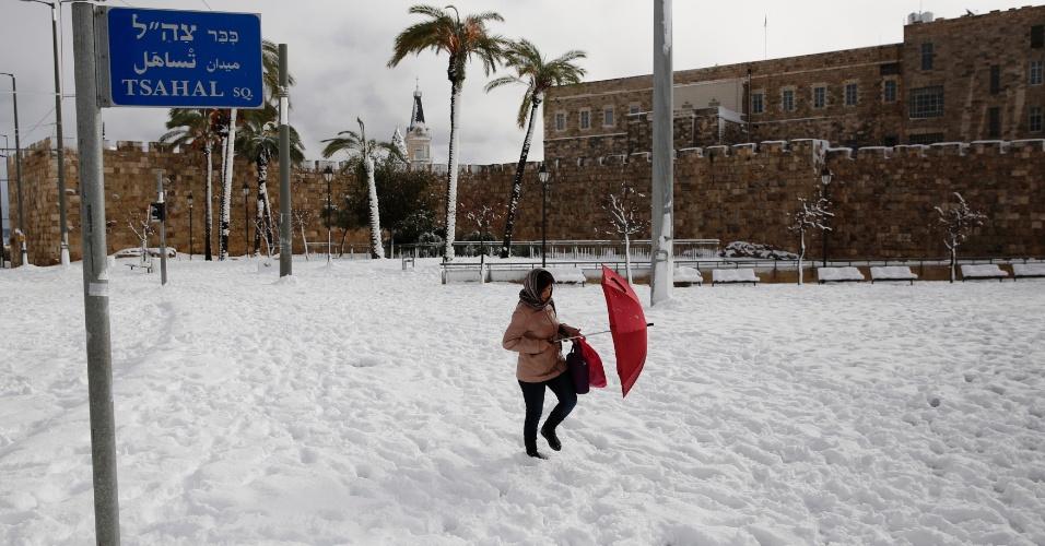 14.dez.2013 - Mulher caminha pela neve na região da Velha Jerusalém, em Israel. O exército israelense tem ajudado os serviços de emergência a remover a neve das ruas e a restaurar a energia elétrica para milhares de pessoas. O nível da tempestade de neve foi o maior em 50 anos