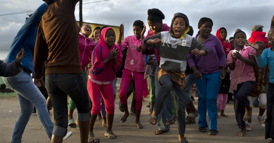 14.dez.2013 - Pessoas dançam próximas à casa para onde foi levado o corpo de Nelson Mandela, na aldeia de Qunu. O corpo do ex-líder sul-africano será enterrado neste domingo (15)