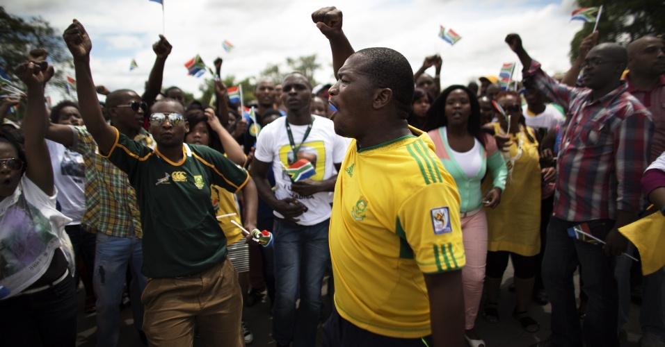 14.dez.2013 - Sul-africanos cantam enquanto esperam a passagem do carro que transporta o corpo de Nelson Mandela em Mthatha