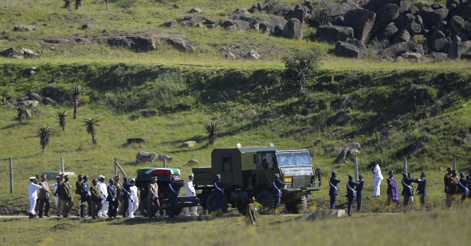15.dez.2013 - 15.dez.2013 - Caixão com corpo do ex-presidente sul-africano Nelson Mandela é escoltado em direção ao local onde vai ocorrer seu funeral, no vilarejo de Qunu. Ele passou a infância no vilarejo e seu corpo será enterrado no local após a cerimônia