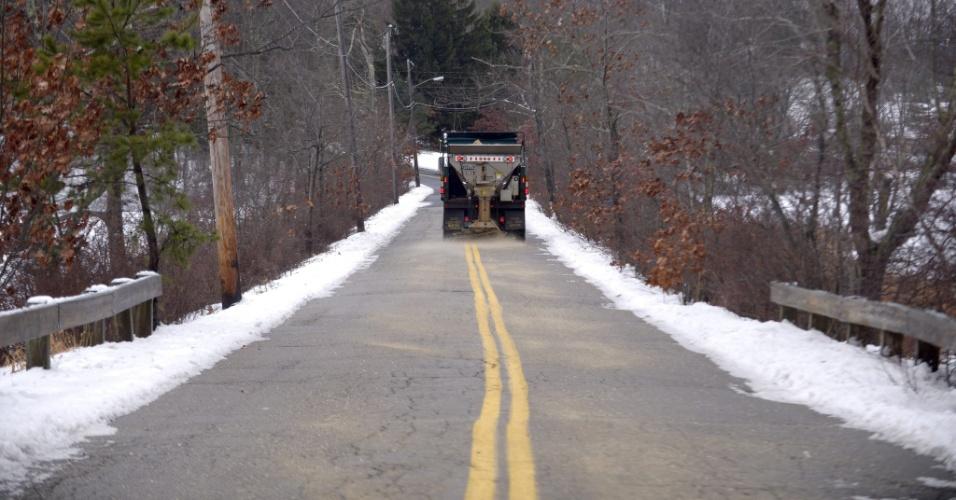 15.dez.2013 - Caminhão espalha sal por estrada em Norfolk, em Massachussets (Estados Unidos), para evitar que seja criada outra camada de neve sobre a via. Na noite anterior, havia uma camada de 15 cm na região, dificultando o tráfego de carros