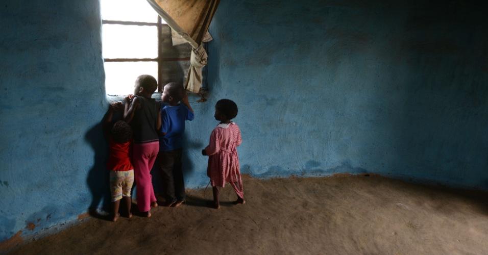 15.dez.2013 - Crianças correm para a janela para ver a movimentação de pessoas reunidar para o funeral de Nelson Mandela a apenas alguns metros da casa onde vivem em Qunu